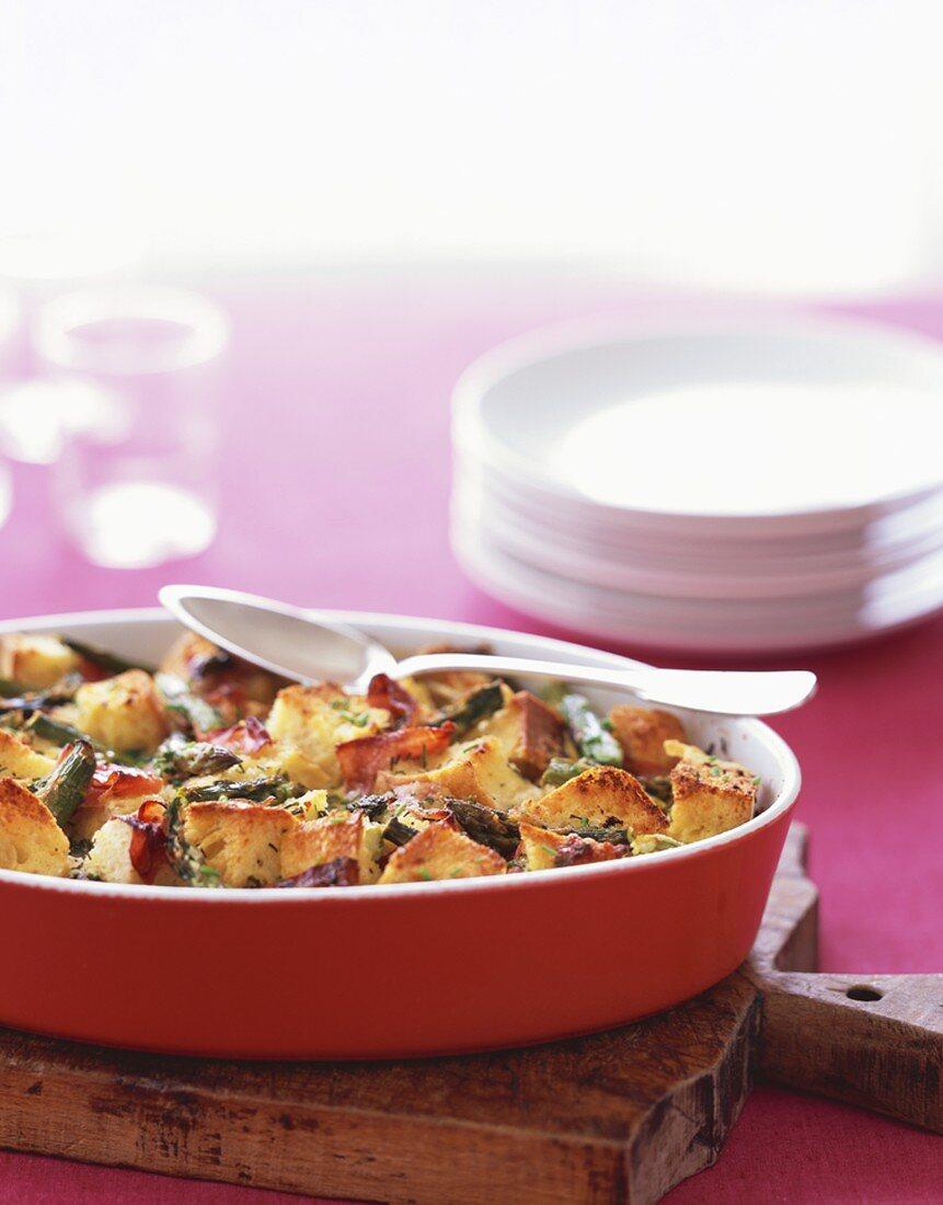 Asparagus and Prosciutto Strata in a Red Casserole Dish