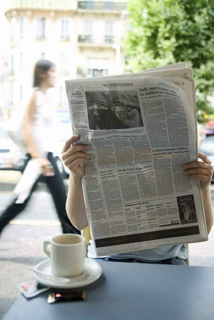 Person Having Coffee and Reading a Newspaper at Outdoor Restaurant
