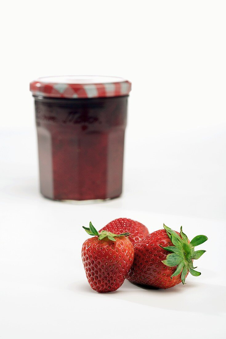 Three Fresh Strawberries with a Jar of Strawberry Jam