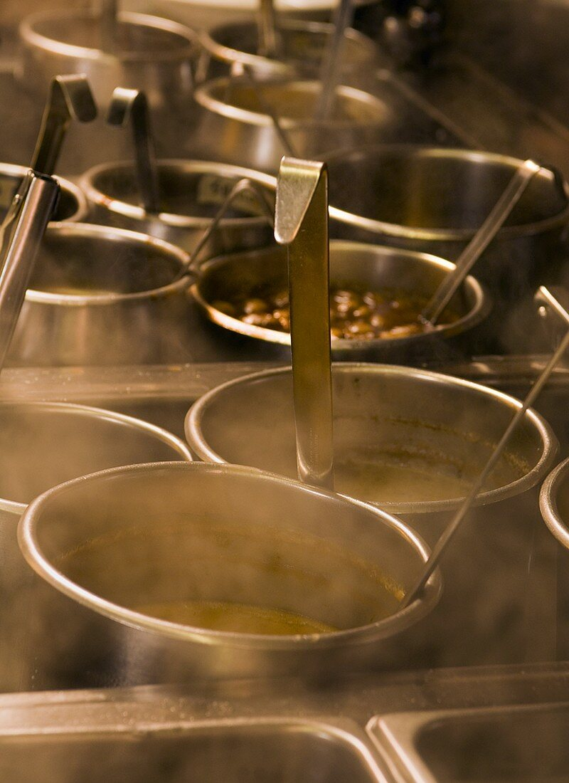 A Variety of Steaming Sauce Pot with Ladels in a Restaurant Kitchen