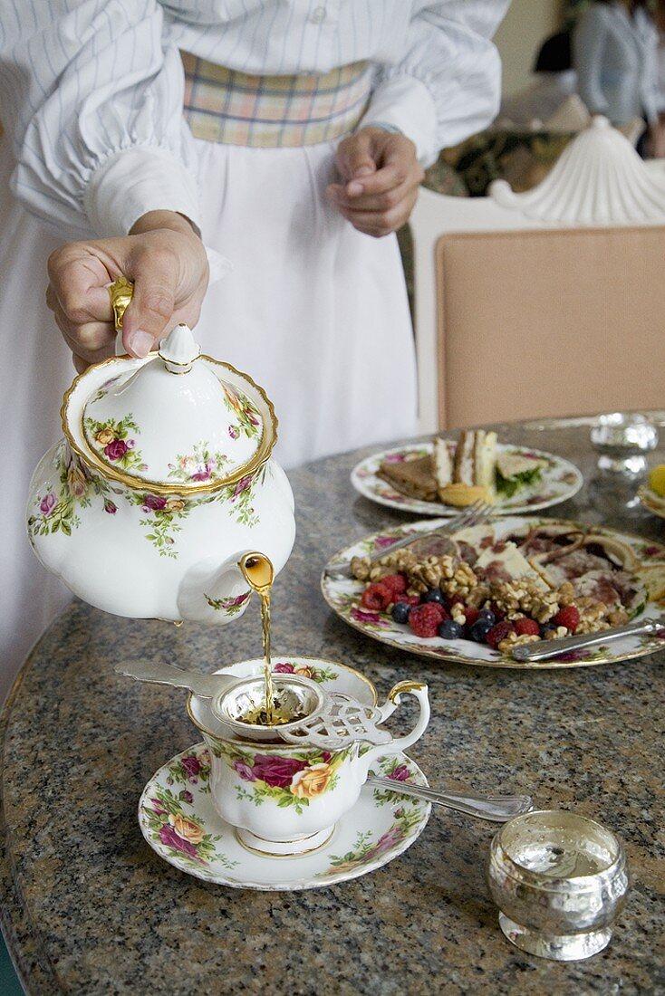Straining Tea into a Porcelain Cup for High Tea