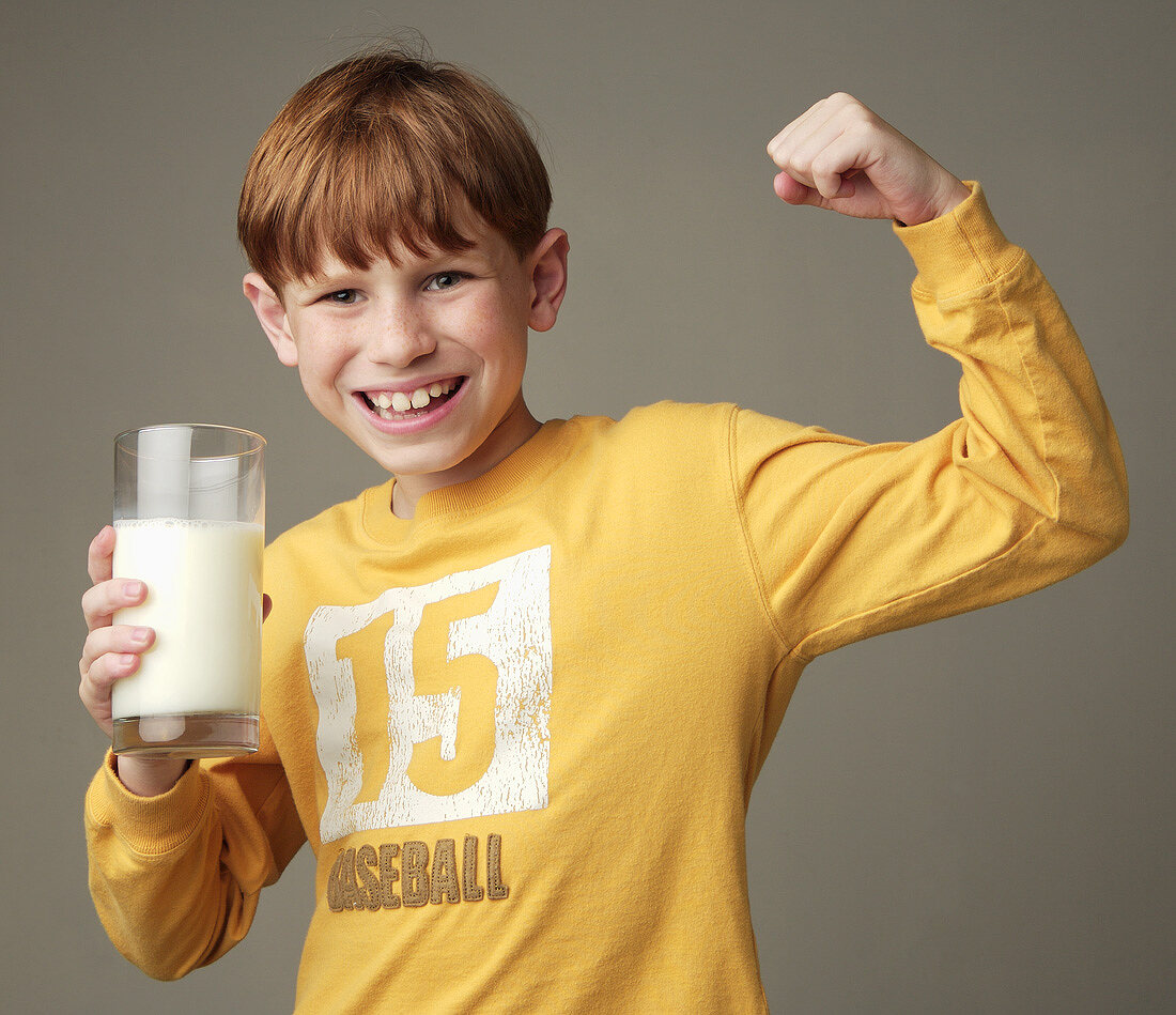 Little Boy Holding a Glass of Milk and Making a Muscle