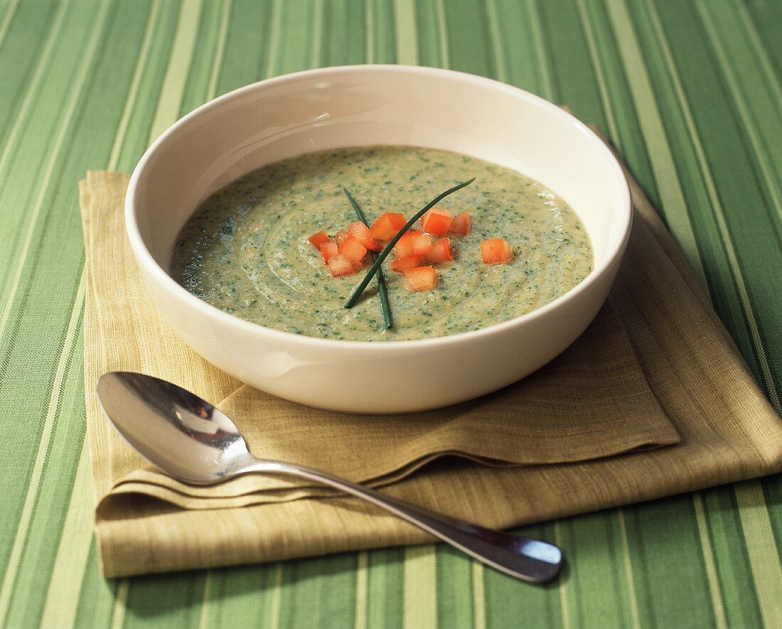 Cold cream of vegetable soup with diced tomatoes and chives