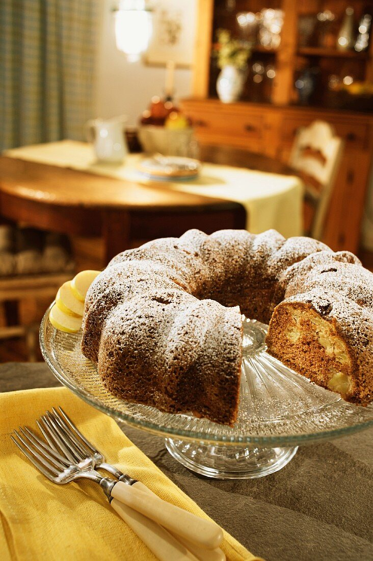 An Apple Spice Bundt Cake on a Glass Cake Stand at Home