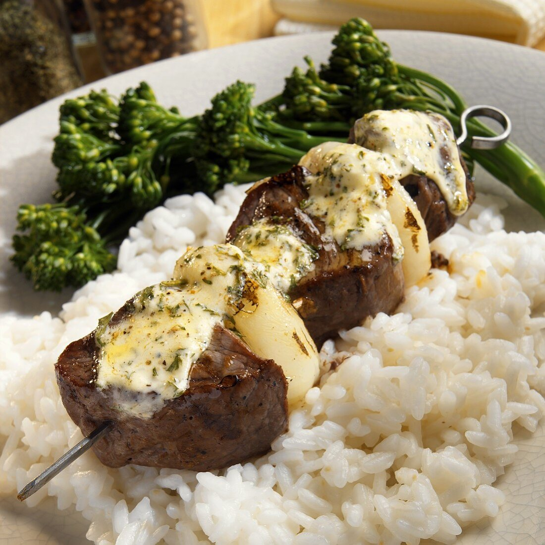 Beef kebab with onions and herb butter on rice