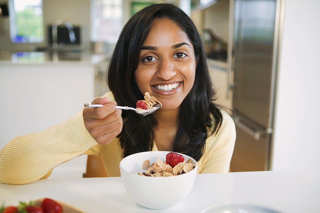 A Young Woman Smiling and Holding a Spoonful of Bran Flake Cereal in Front of a Bowl of Cereal