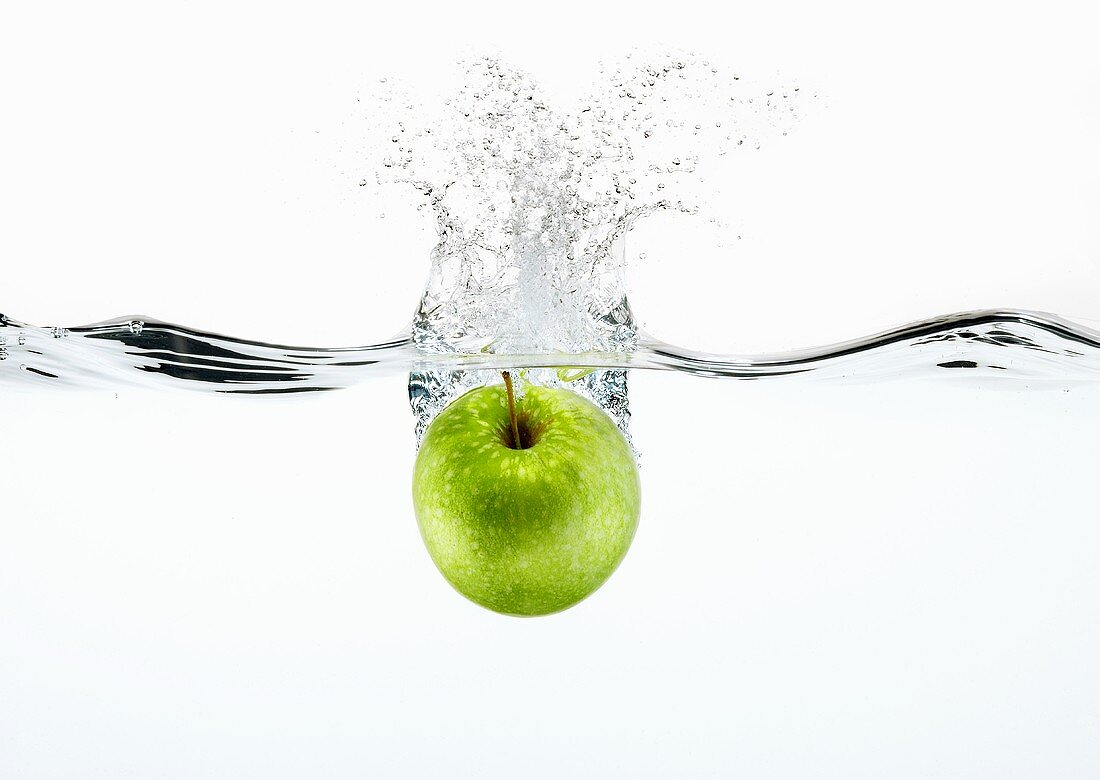 A Granny Smith Apple Splashing into Water