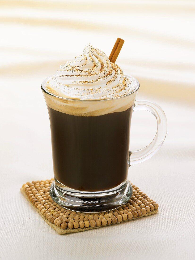 An Irish Coffee in a Glass Mug with a Cinnamon Stick