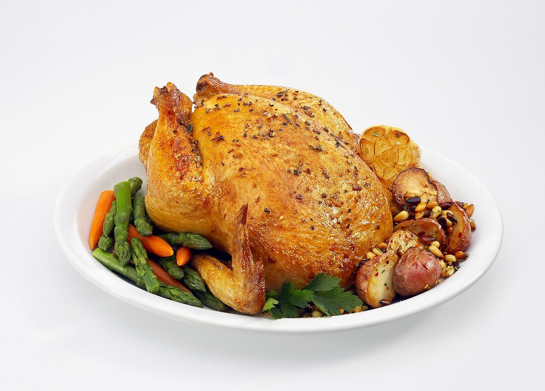 Roasted Chicken on a Platter with Asparagus, Carrots and Potatoes on White