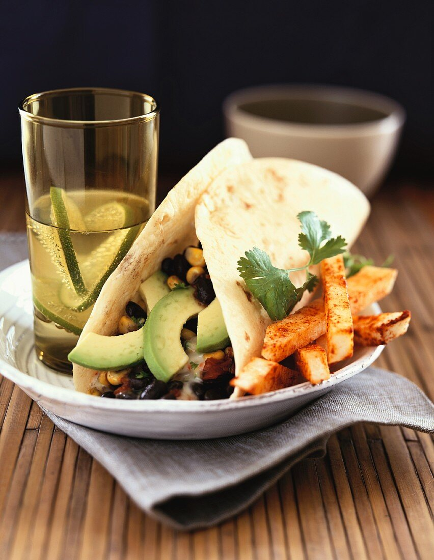 A Soft Shell Taco with Black Beans, Corn and Avocado Slices