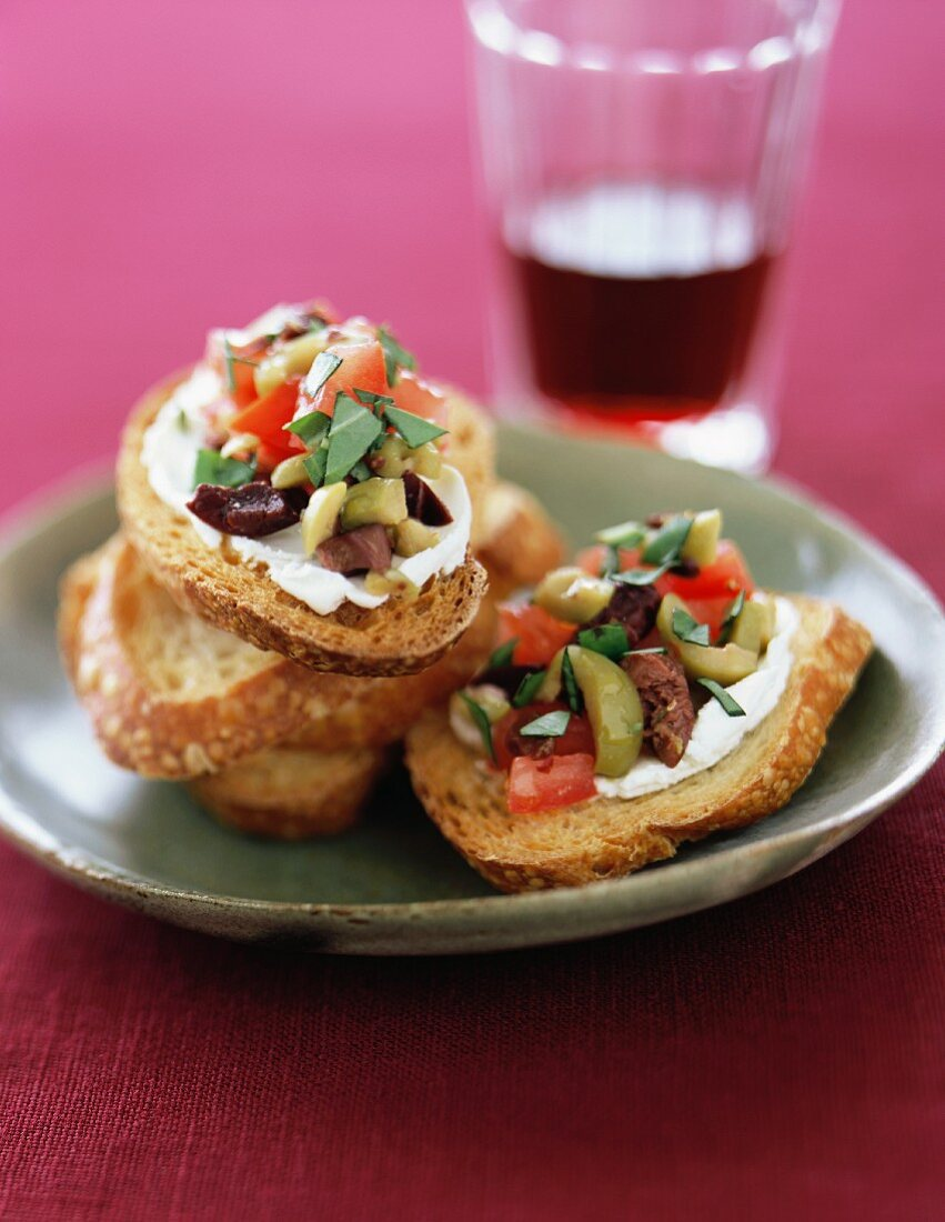 Bruschetta with Olives on a Plate with a Glass of Red Wine