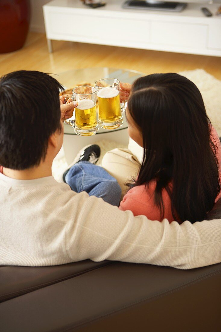 Couple on sofa clinking glasses of beer