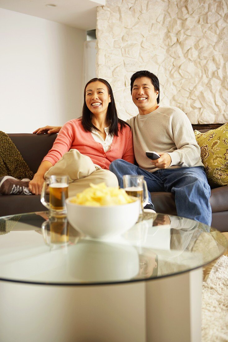 Couple on sofa watching television with crisps and beer