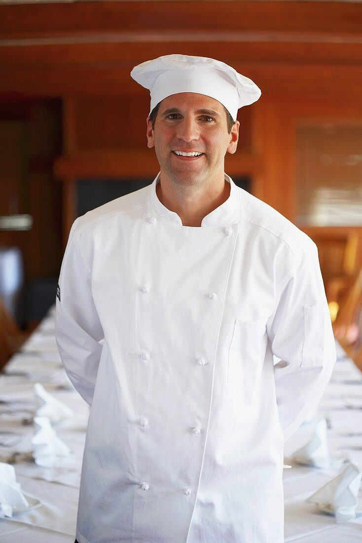 Chef in front of a laid table in a restaurant