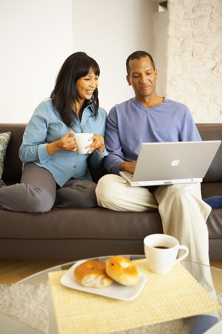 Woman with cup of coffee beside man with computer on sofa