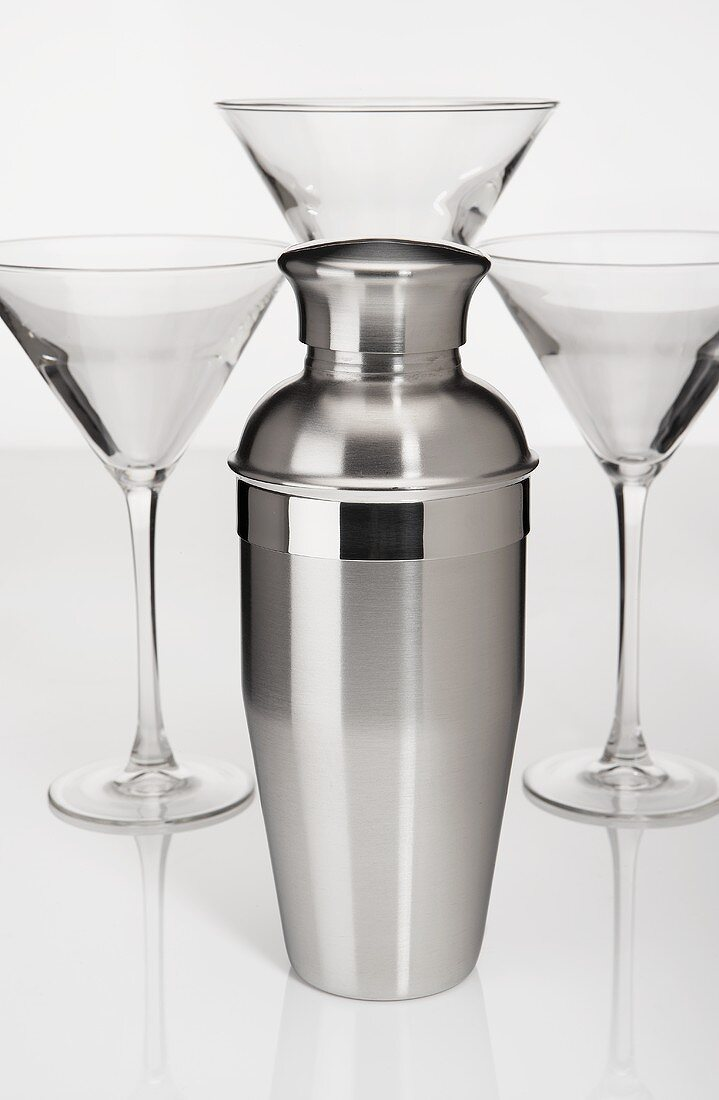 A Cocktail Shaker with Three Empty Martini Glasses