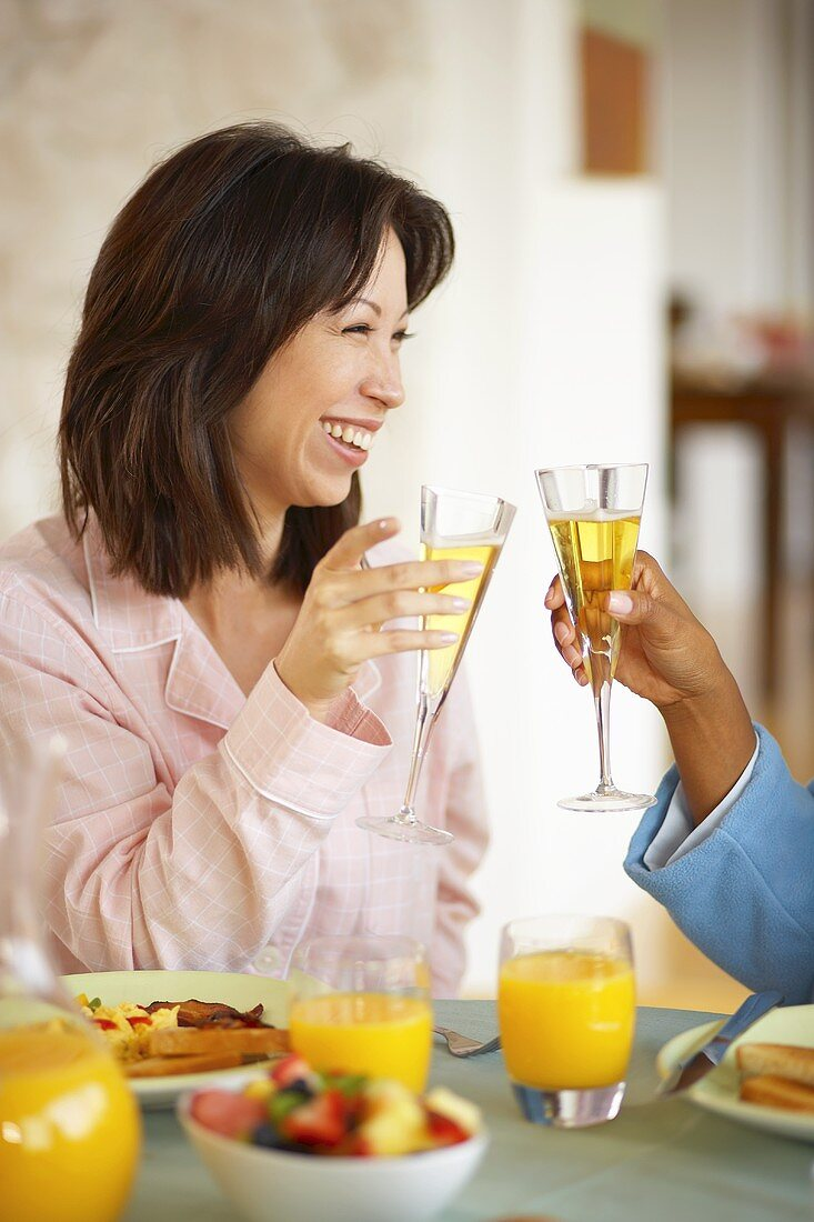 Couple clinking champagne glasses at breakfast