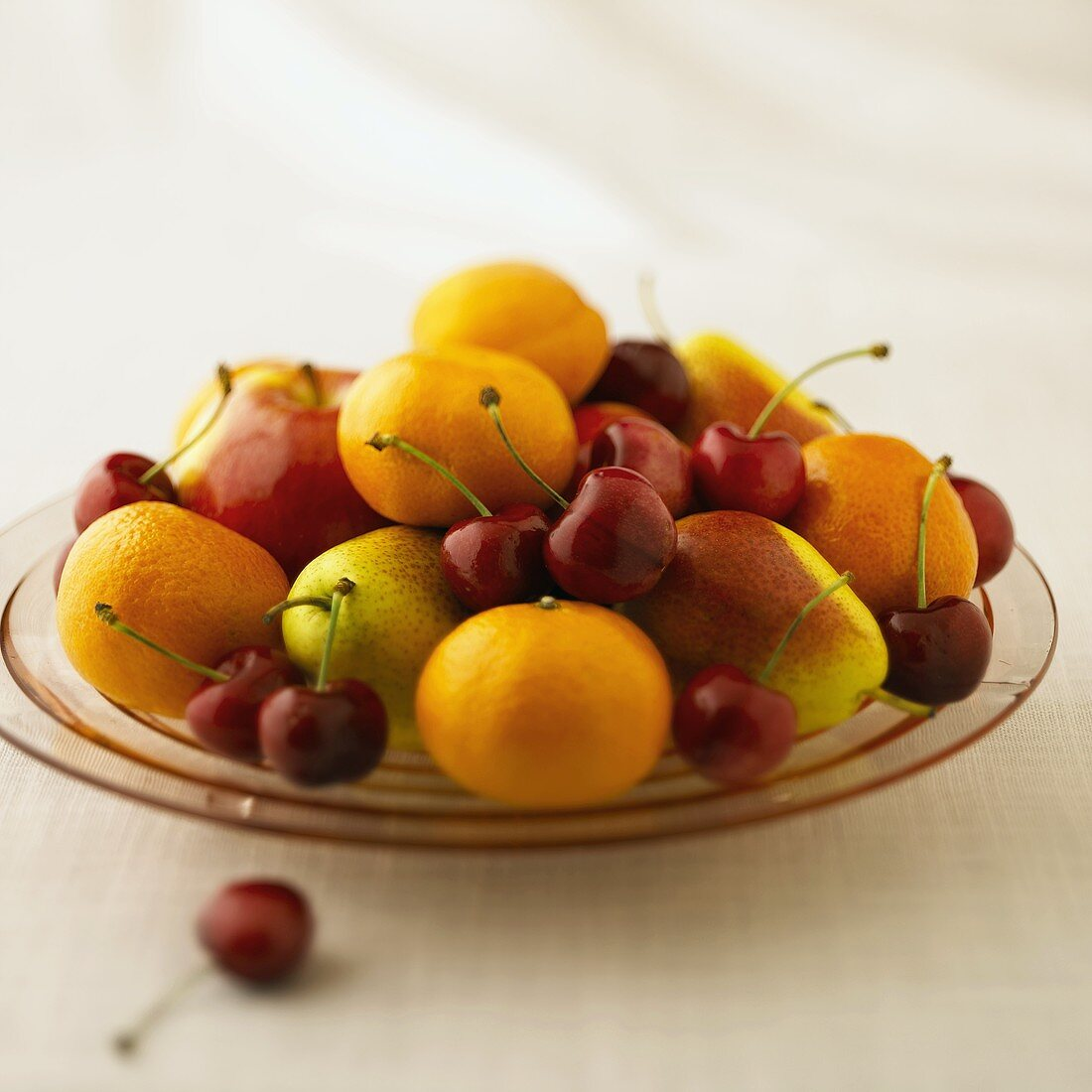 Clementines, Forelle Pears and Cherries on a Pink Glass Plate