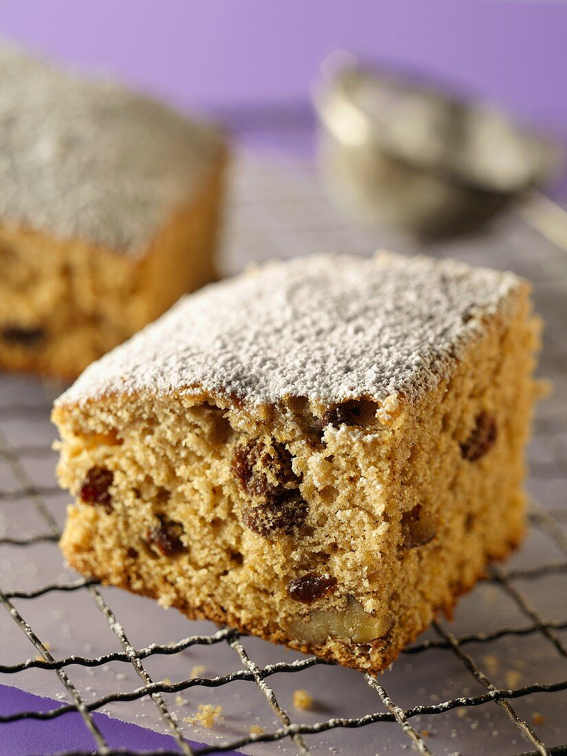 A Piece of Spice Cake with Powdered Sugar on a Cooling Rack