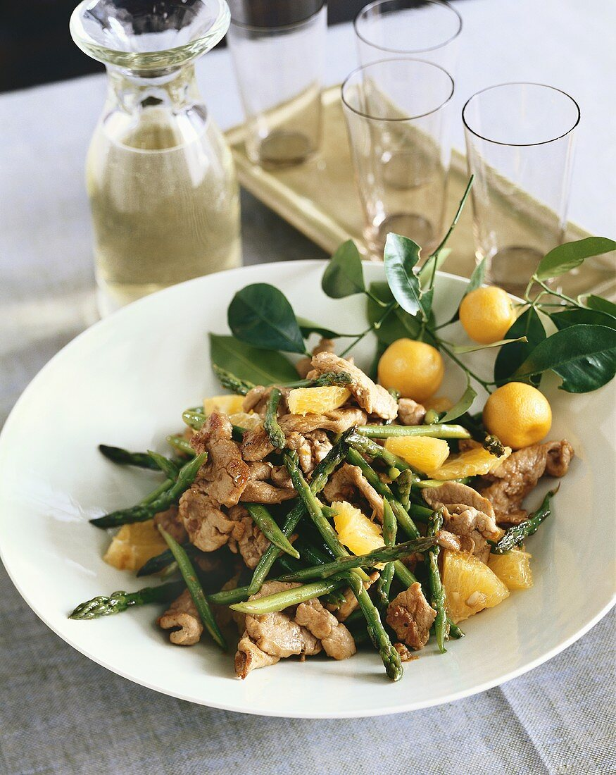 Pork, Asparagus and Orange Stir Fry in White Bowl; White Wine in Decanter with Glasses