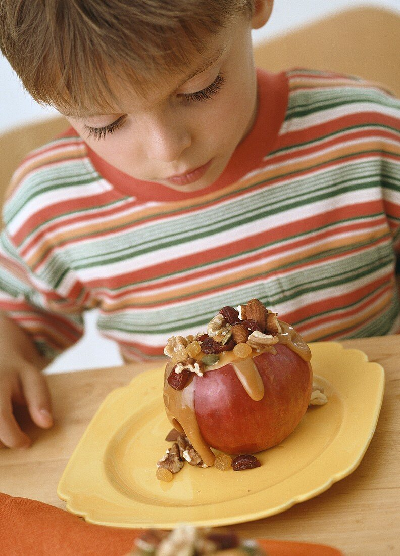 Boy eating apple with nut stuffing and caramel sauce