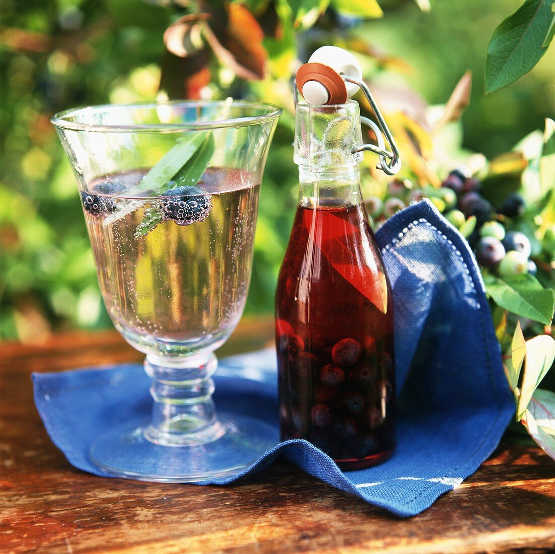 Apple schorle with blueberries, bottle of blueberry vinegar