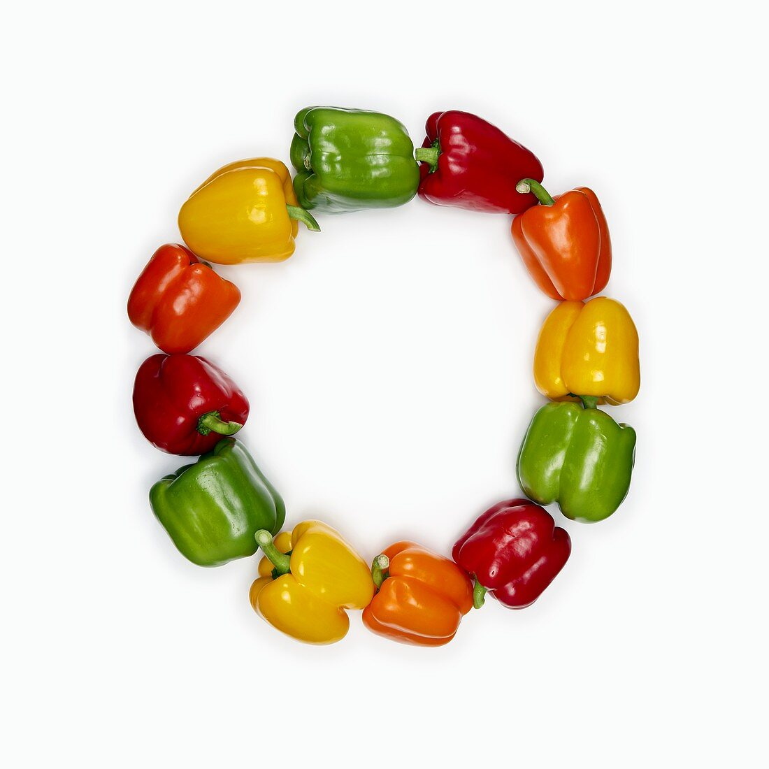 Red, yellow and green peppers, arranged in a circle