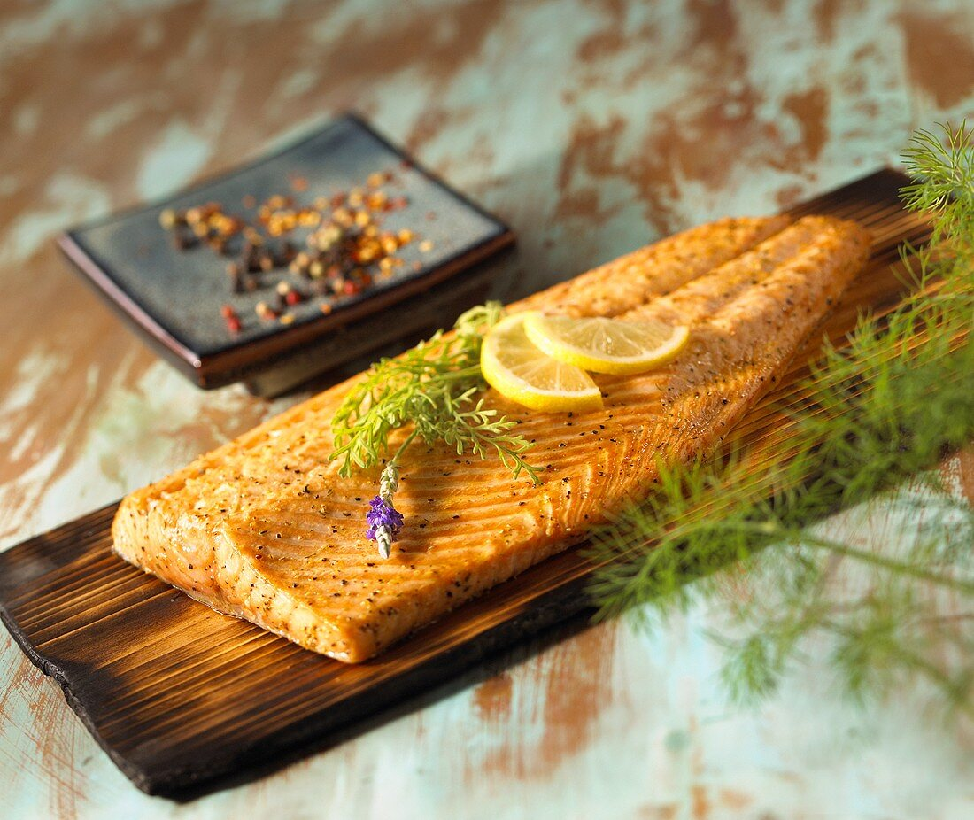 Salmon Fillet Cooked on a Cedar Plank with Herb and Lemon Garnish