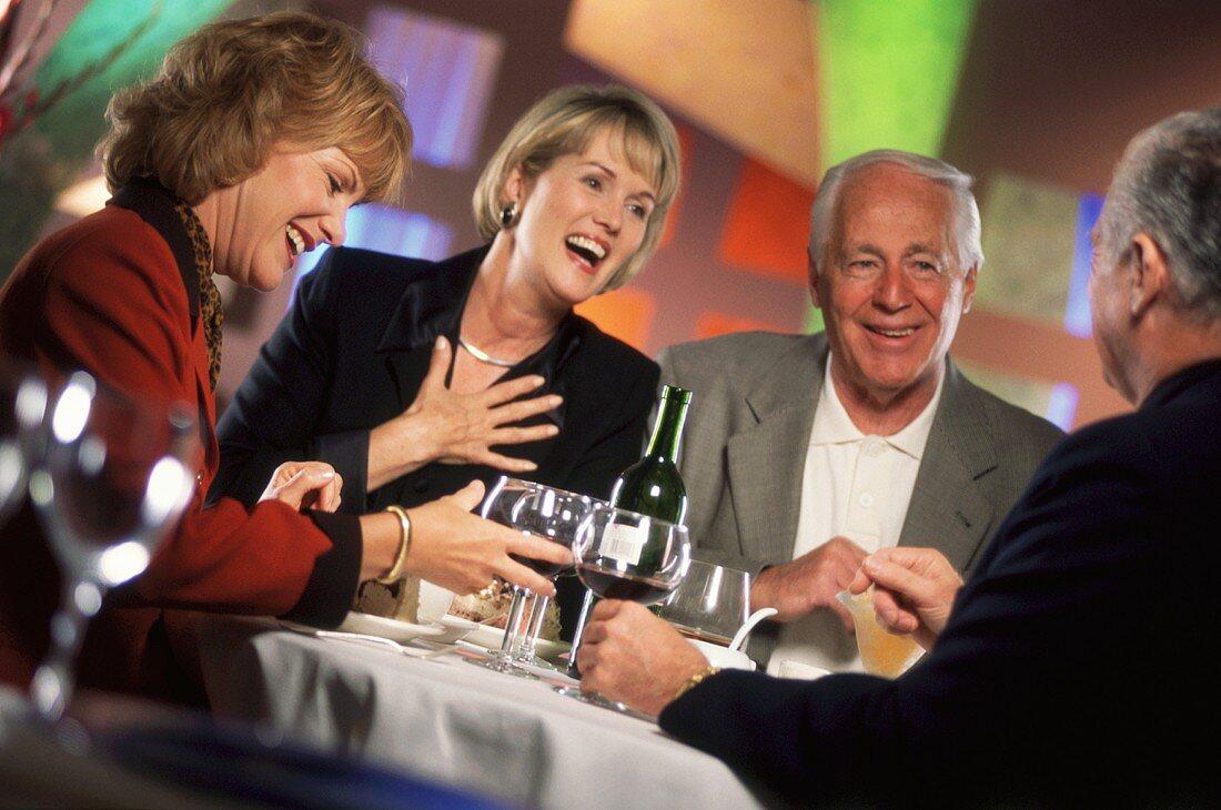 Zwei ältere Pärchen unterhalten sich bei Getränken im Restaurant