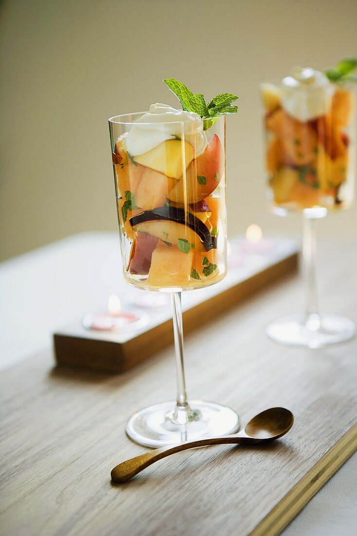 Fruit cocktail with cream & fresh mint in dessert glasses