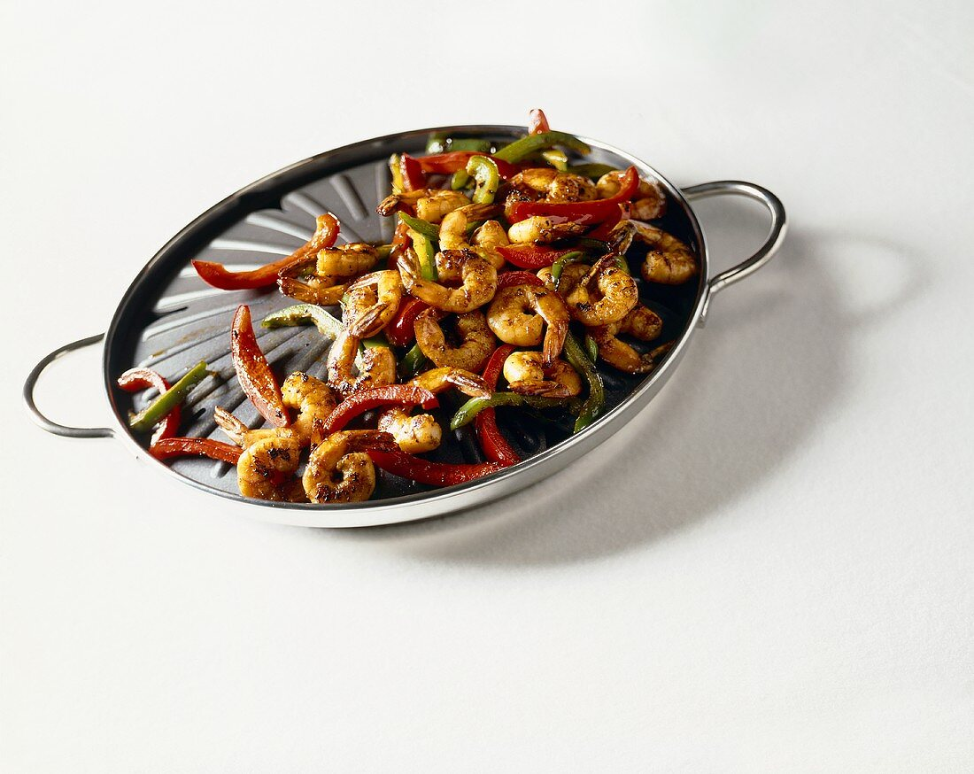 Shrimp and Sliced Bell Peppers on a Stove Top Grill; White Background