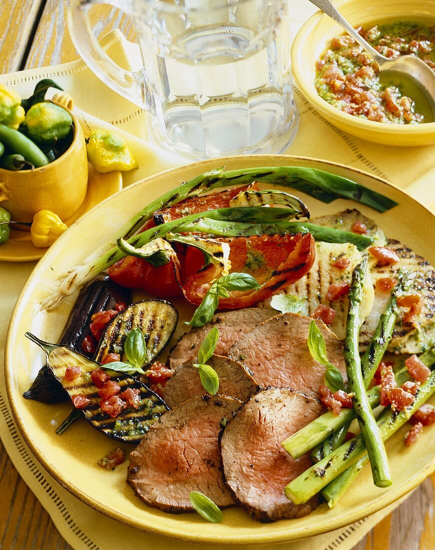 Sliced Grilled Beef with Grilled Vegetables on a Yellow Plate