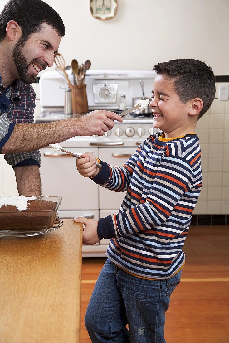 Father and son having fun icing a chocolate cake