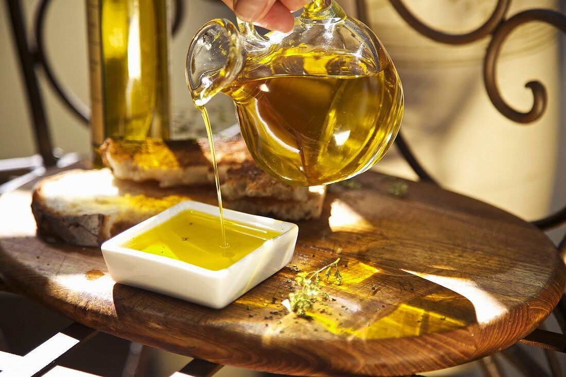 Hand Pouring Organic Cold Press Olive Oil into a Small Dish