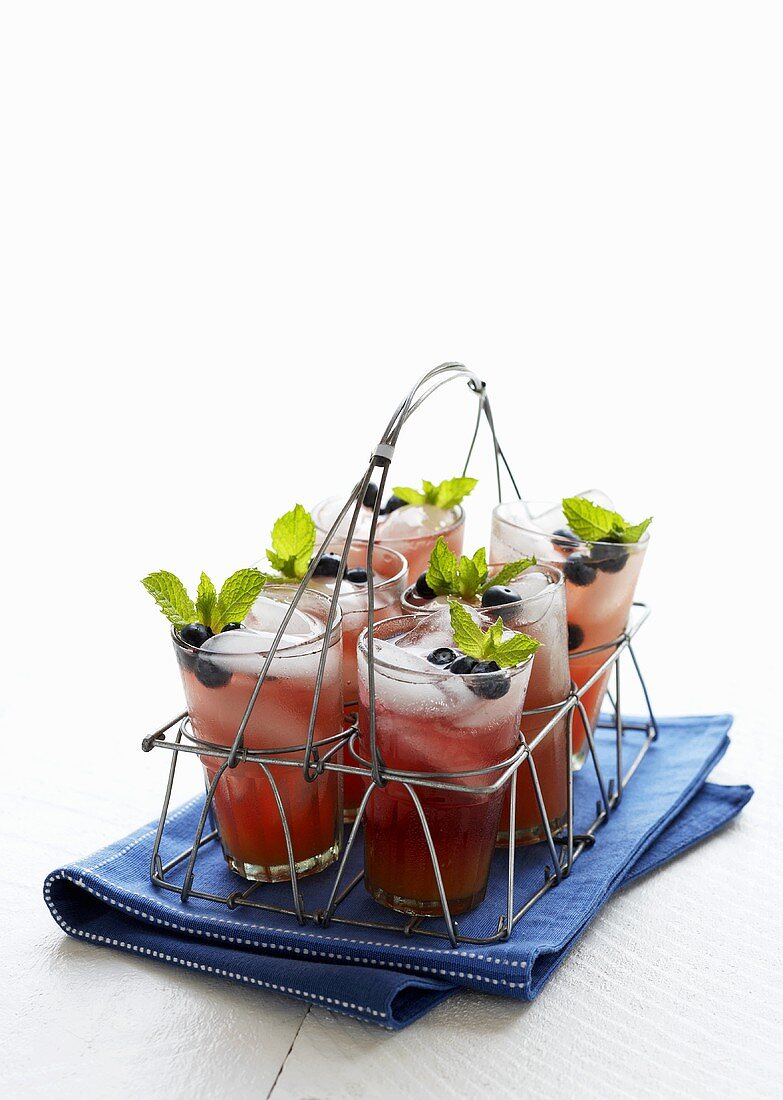 Glasses of Blueberry Lemonade in a Wire Drink Carrier; On a Blue Dish Cloth