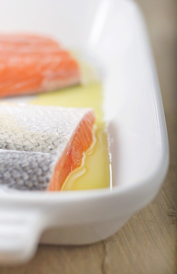 Raw Salmon Fillets with Skin in Olive Oil in Baking Dish