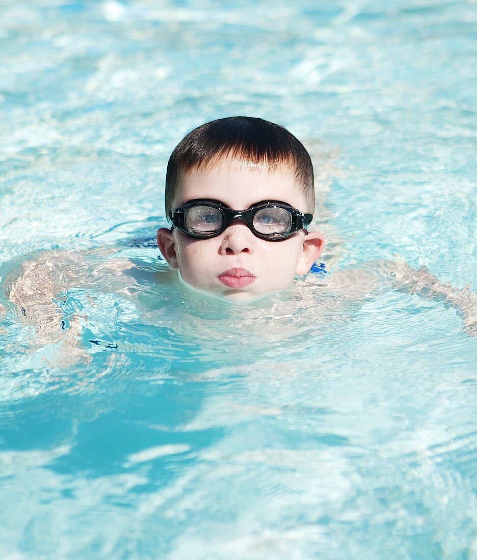 Little Boy Swimming in a Pool; Wearing Goggles