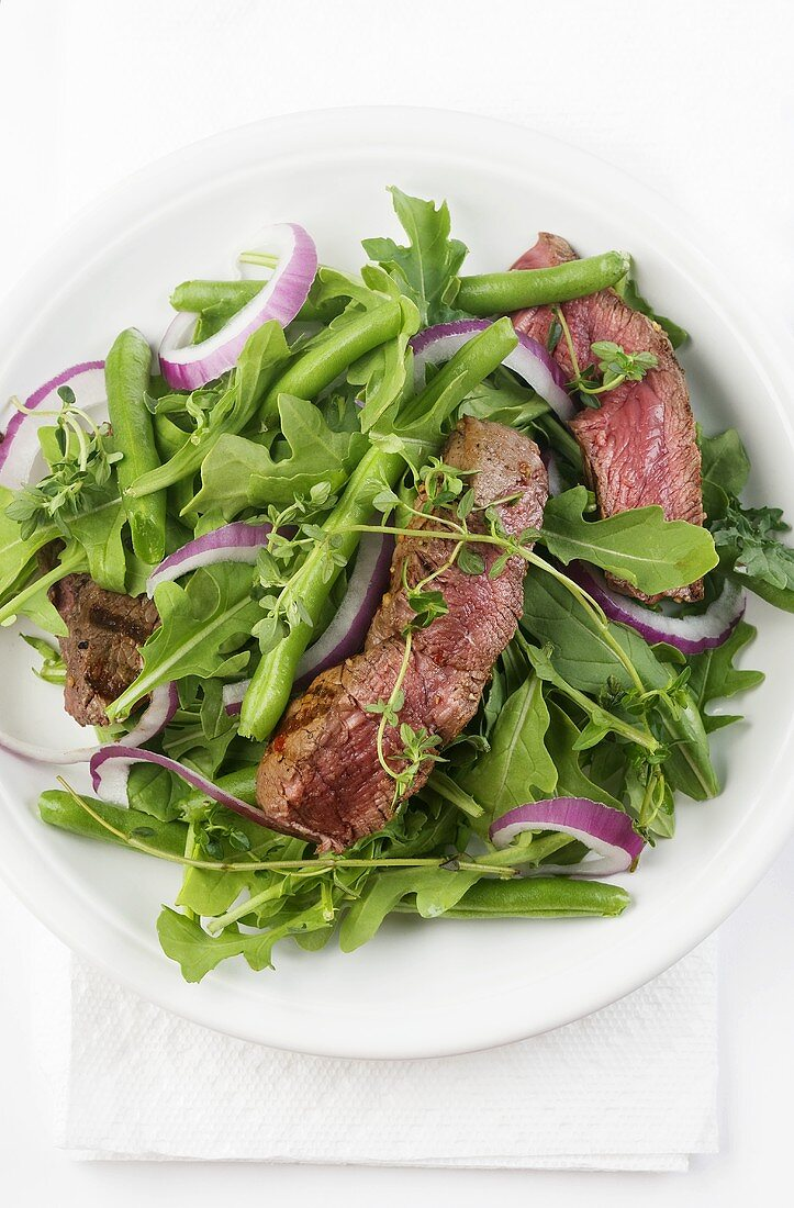 Sliced Grilled Steak Salad with Greens and Onion