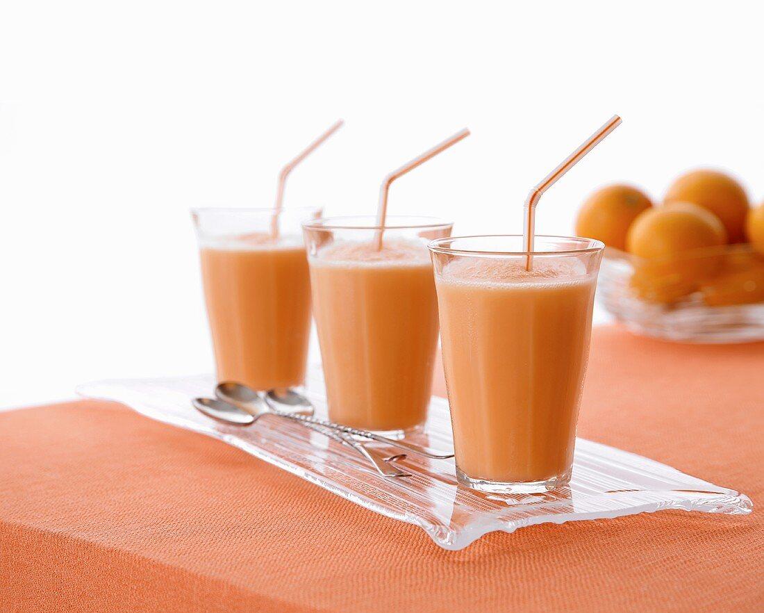 Three creamsicle smoothies (cantaloupe melon and orange juice)