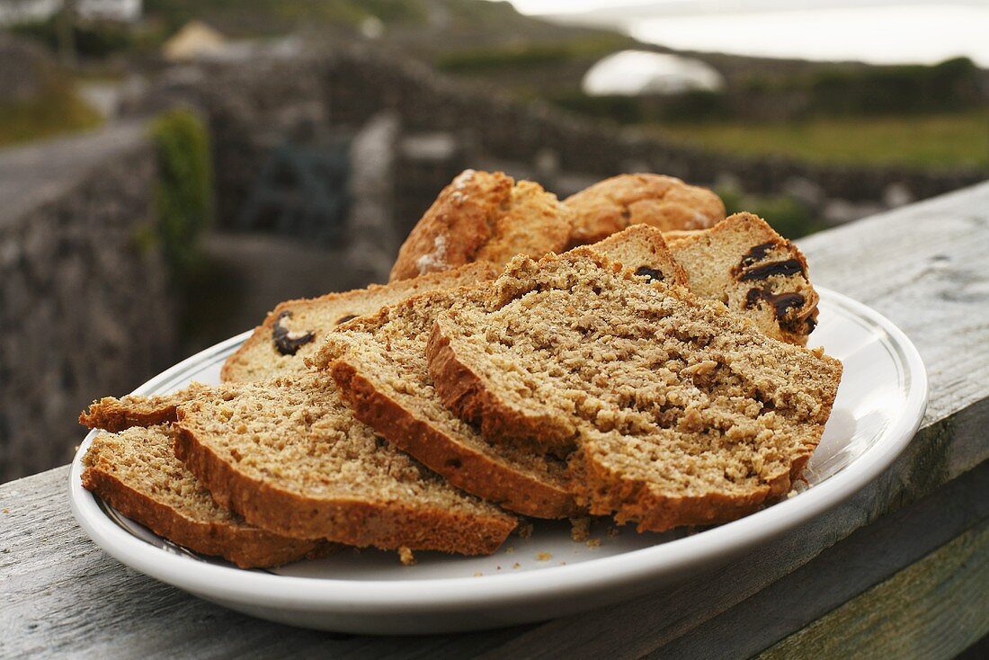 Platter of Bread and Scones on Outdoor Railing Overlooking Stone Fences; Aran Island, Ireland
