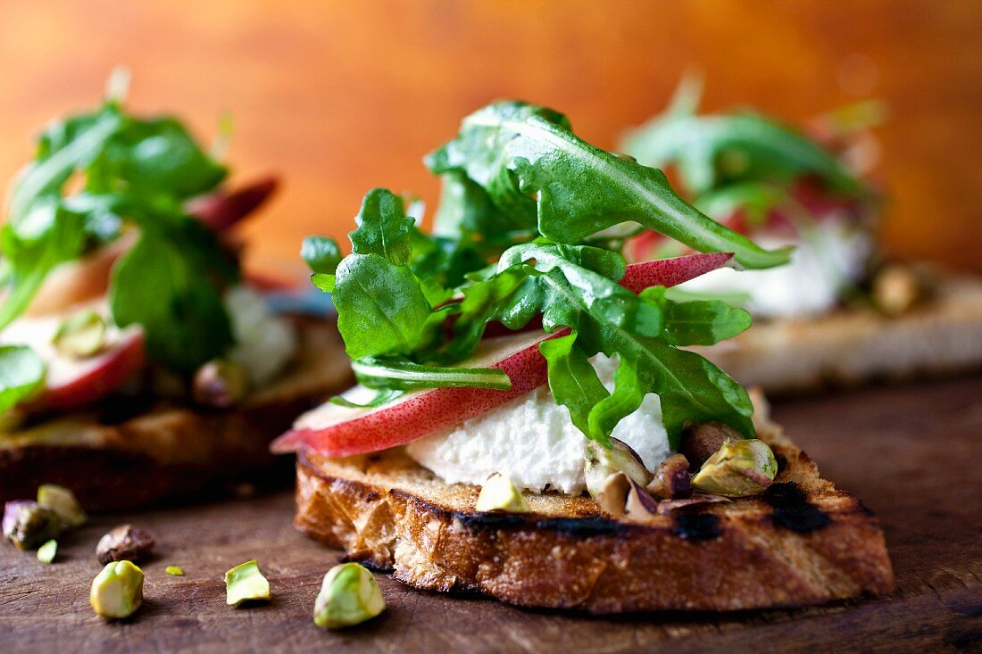 Crostini Topped with Cheese, Pear, Nuts and Greens