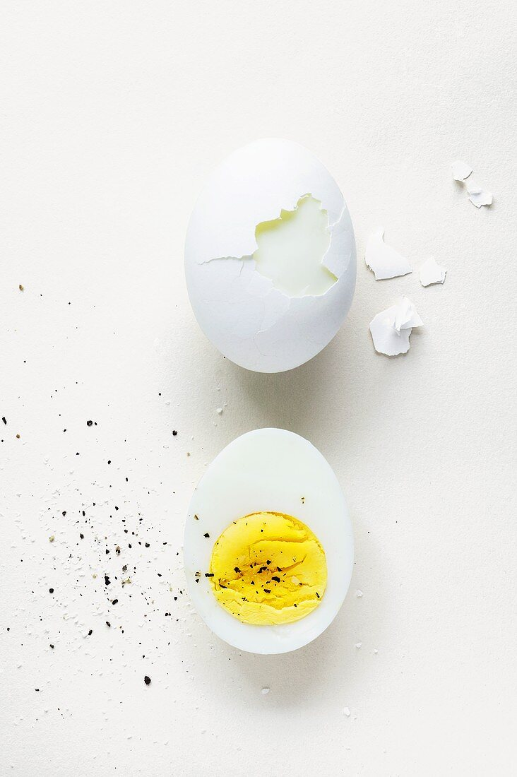 Half of a Hard Boiled Egg with Pepper; Partially Peeled Hard Boiled Egg