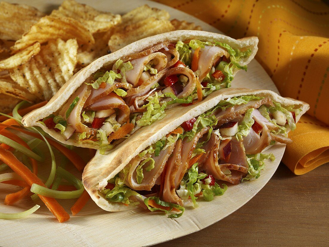 Shaved Pork Pita Sandwich with Chips and Carrot and Celery Garnish