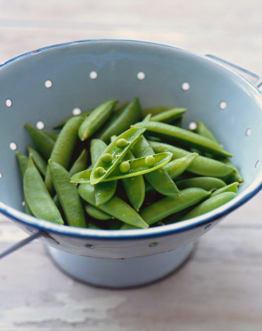 Fresh Pea Pods in a Colander; One Split Open