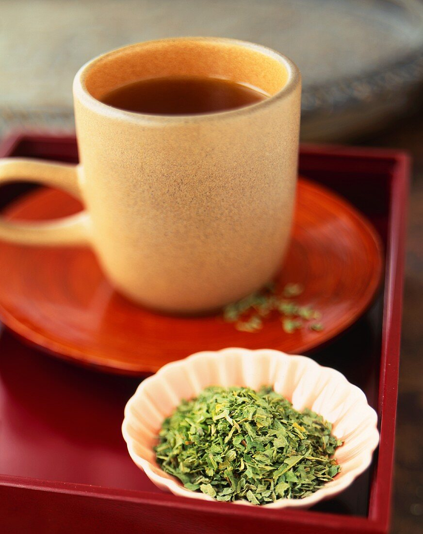 Cup of Tea with a Small Dish of Loose Nettle Tea Leaves