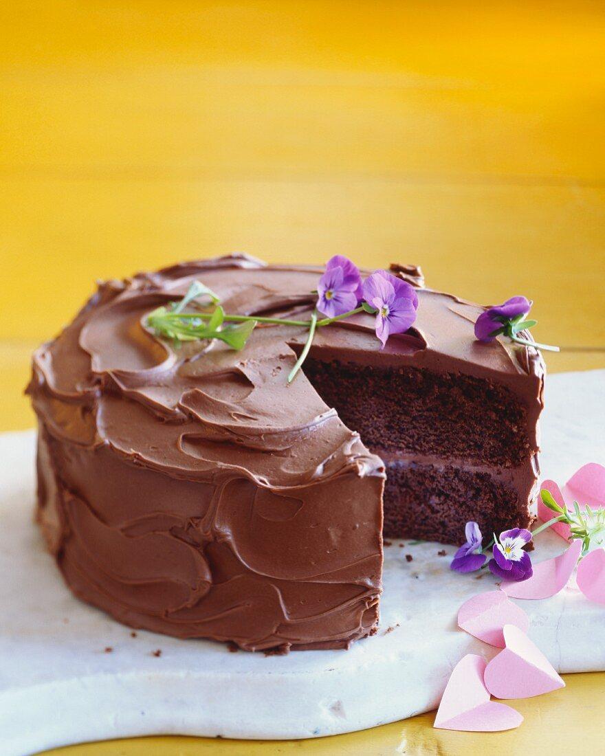 Schokoladencremetorte mit lila Blumen und Papierherzen