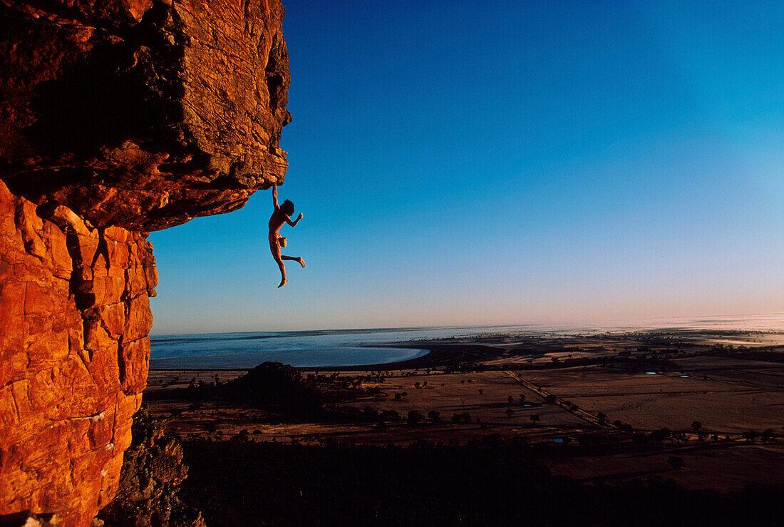 Freeclimber Stefan Glowacz hanging from rock, Mount Arapiles, Australia