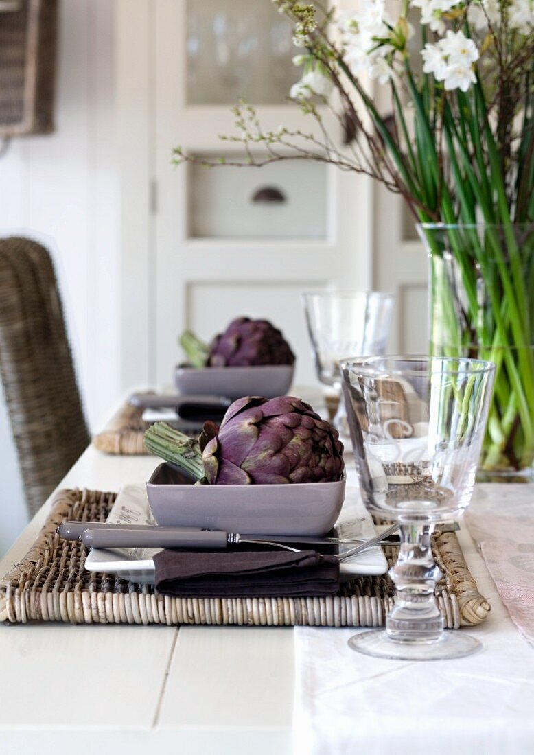 Place settings with artichokes on a woven place mat
