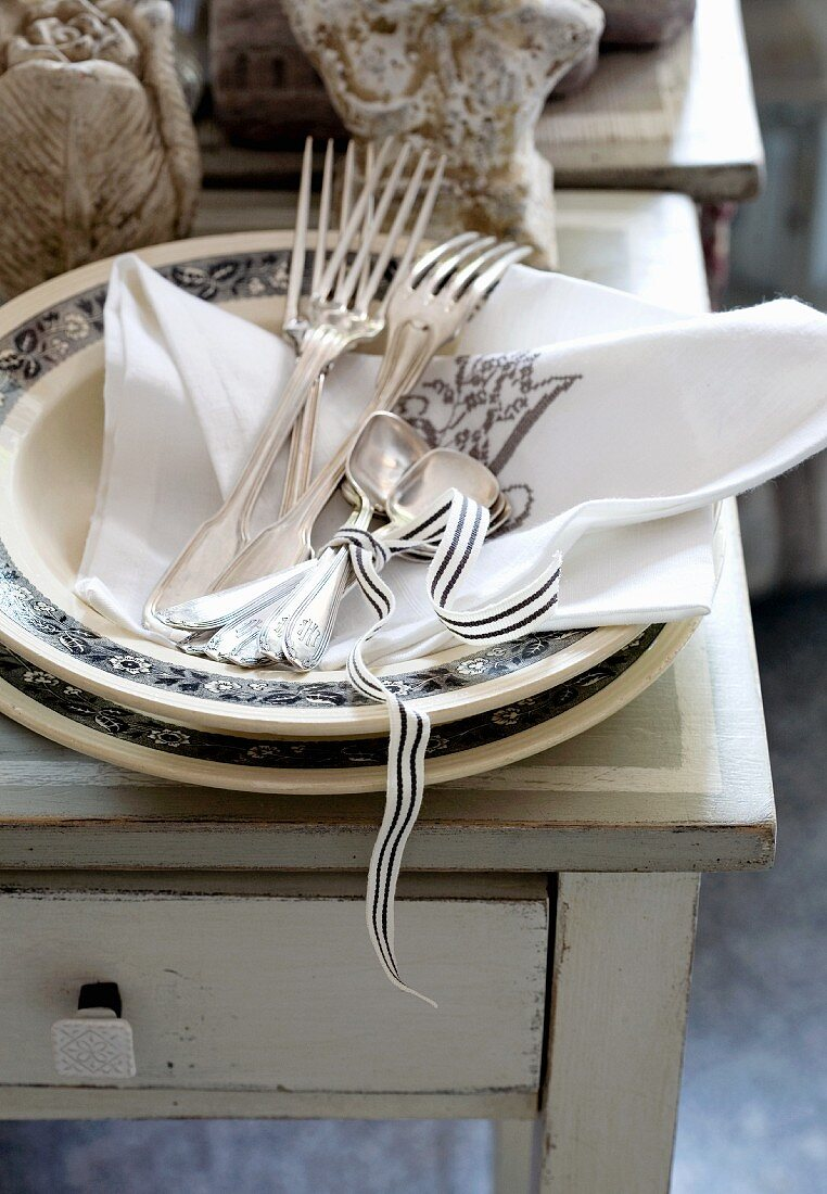 A stack of plates and silver cutlers in a country-house style