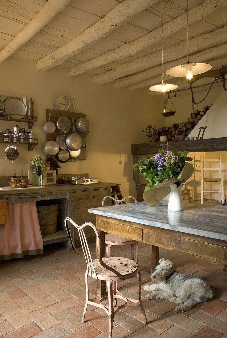 A rustic kitchen with a dining area and a dog lying on a Mediterranean terracotta floor